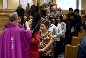 Members of the congregation form a line in front of Rev. Theodore Olson as he places ash on foreheads during Ash Wednesday mass at St. Pius V Catholic Church in Buena Park early Wednesday morning. ADDITIONAL INFO: ashweds - 02/17/10 - Photo by MARK RIGHTMIRE, THE ORANGE COUNTY REGISTER